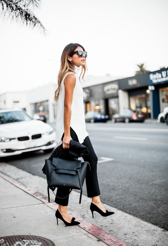 a long white sleeveless top with slits, black cropped pants, black bow shoes and a black tote