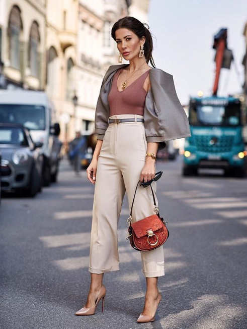 a mauve top, a statement necklace, neutral trousers, nude pumps, a red bag, a grey cropped blazer and statement earrings