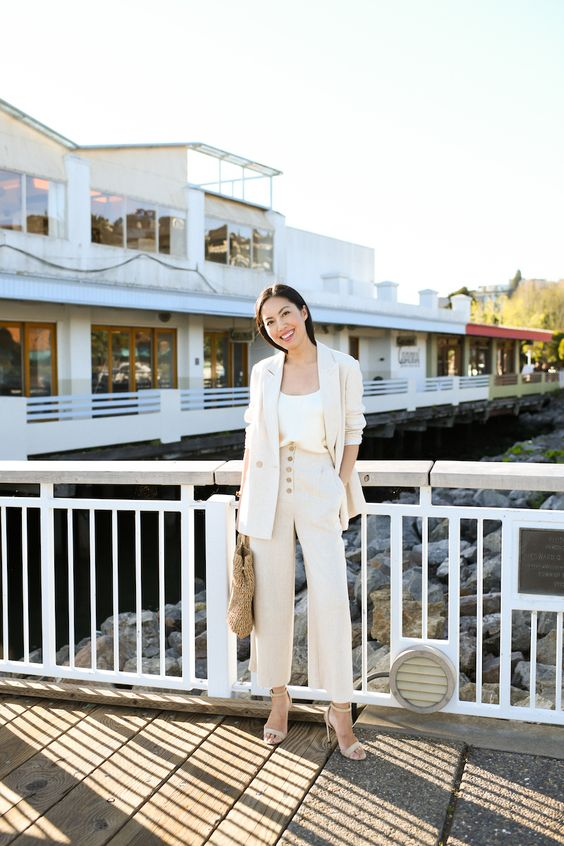 a neutral linen pantsuit, a white top, nude heels, a straw bag for a chic summer work look