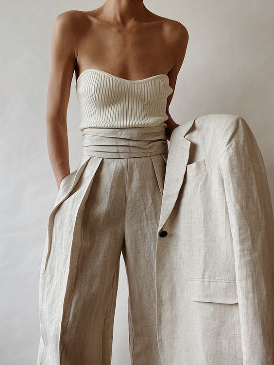 a neutral linen pantsuit with an oversized blazer, pleated pants, a strapless top is chic