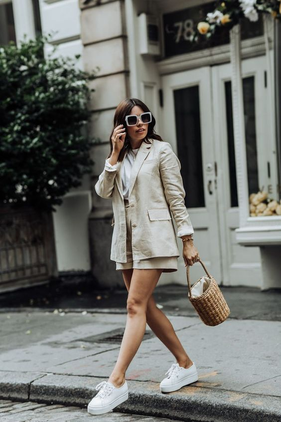 a neutral linen shorts suit with a white t shirt, white platform sneakers and a basket bag