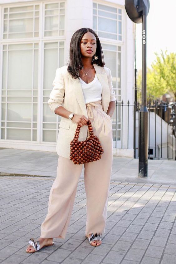 a neutral linen suit with an oversized blazer, pretty slippers, a beaded bag and a white top for summer