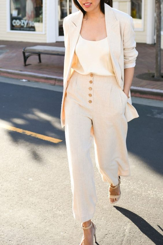 a neutral linen suit with wideleg pants on buttons, an oversized blazer, a silk top and tan shoes