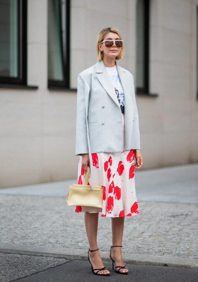 a printed t-shirt, a bright printed slip skirt, black strappy shoes, a striped blazer and a yellow bag
