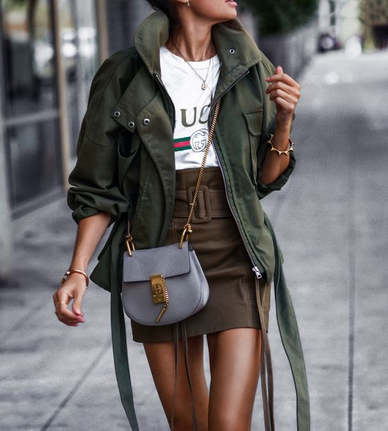 a printed t shirt, a taupe mini skirt, a green army jacket, a grey crossbody bag and gold touches