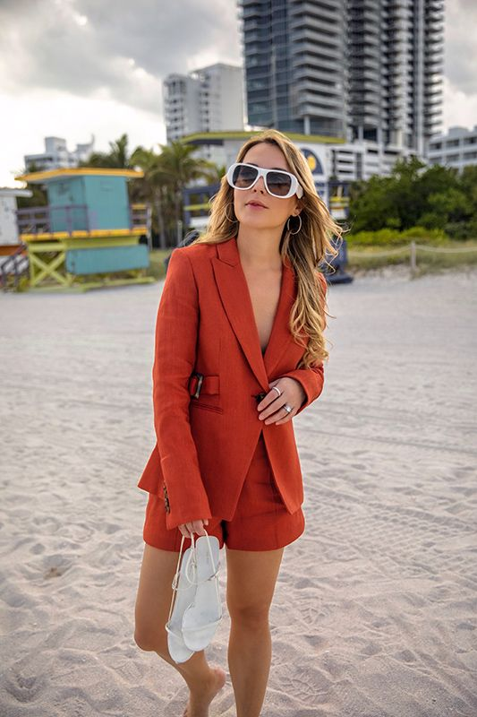 a red linen shorts suit with a fitting blazer, white strappy sandals and white frame sunglasses