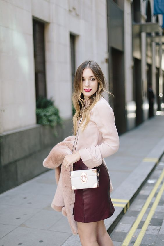 a refined outfit with a blush shirt and a burgundy leather mini skirt, a white bag