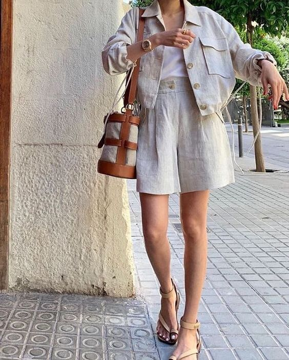 a relaxed linen suit with wideleg shorts and an oversized blazer, white top, nude strappy sandals and a bucket bag