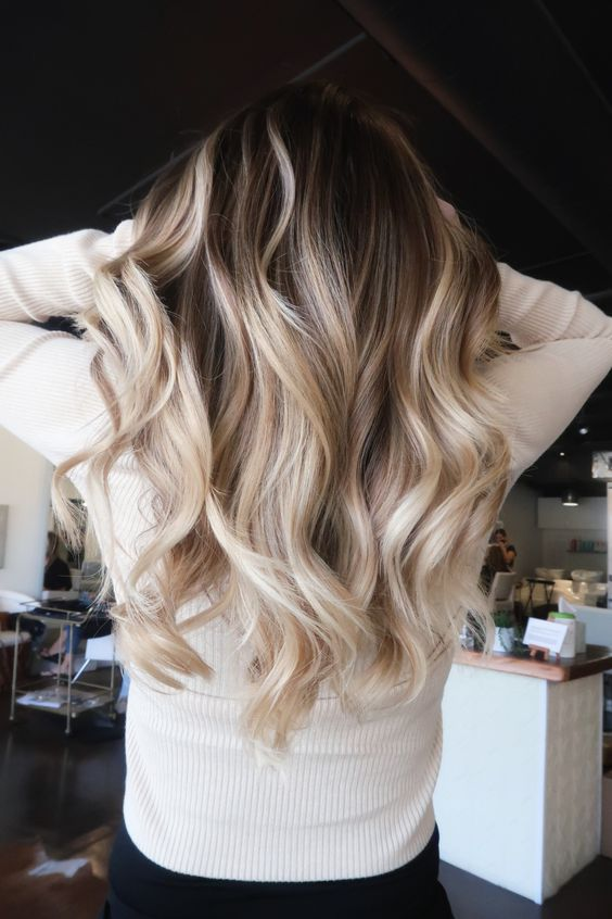a rooty blonde balayage with coffee and vanilla hues and waves is a gorgeous solution that catches an eye