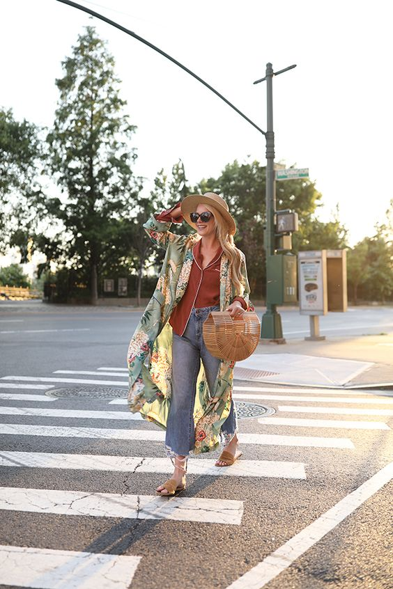 a rust-colored pjs-like shirt, blue jeans, nude slippers, a green floral kimono, a hat and a wooden bag