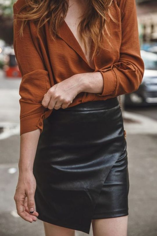 a rust-colored shirt, a black asymmetrical leather mini for a bold and chic look this spring