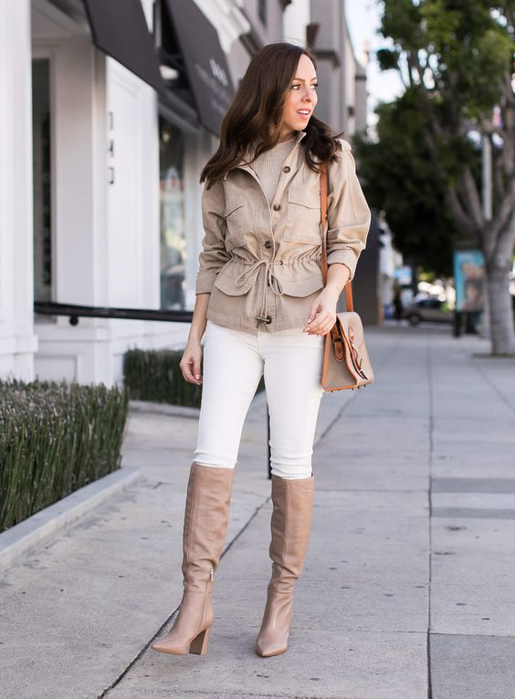 a spring look with a neutral top, white skinnies, a tan safai jacket, tan knee boots and a grey bag