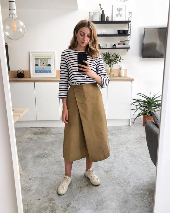 a striped black and white top, a tan wrap A-line midi skirt and neutral sneakers for every day