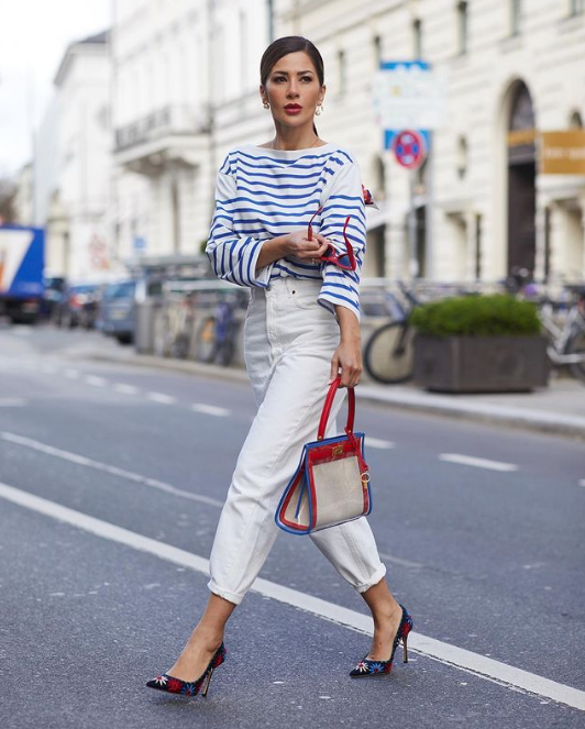 a striped blue and white top, white high waisted pants, floral shoes and a white, red and blue bag