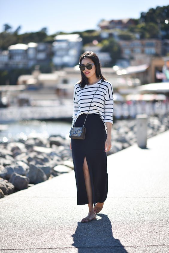 a striped top, a navy midi slit skirt, a black crossbody bag and nude sandals for a coastal look