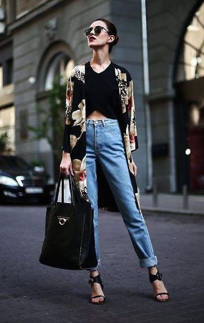 a trendy look with a black crop top, blue jeans, black sandals, a black floral print duster and a black tote