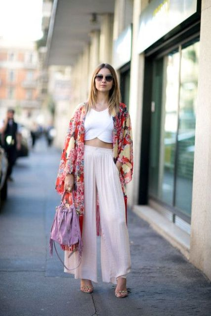 a trendy look with a white cropped top, blush wideleg pants, a bold floral kimono and a lilac bag
