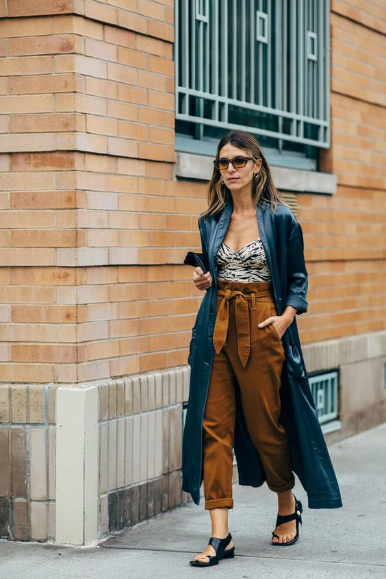 a very chic summer look with a printed strapless top, rust-colored paperbag waist pants, black sandals, a navy duster and a clutch