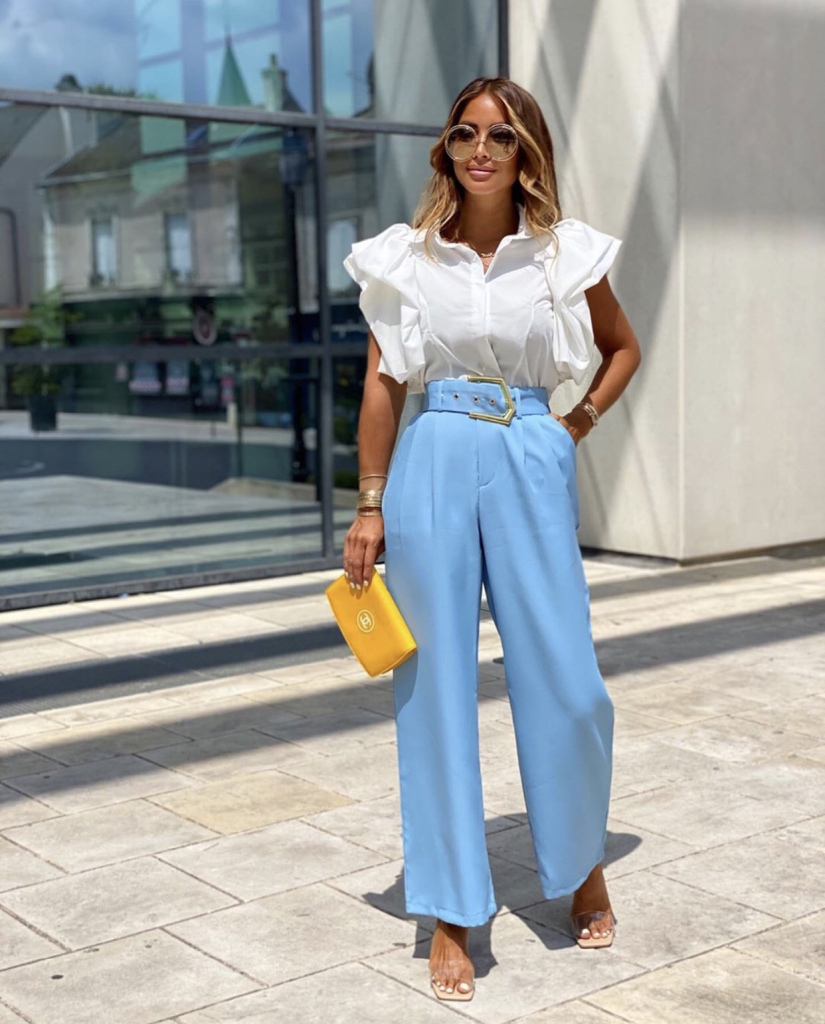 a white blouse with ruffles, blue trousers with light pleating, sheer shoes and statement sunglasses