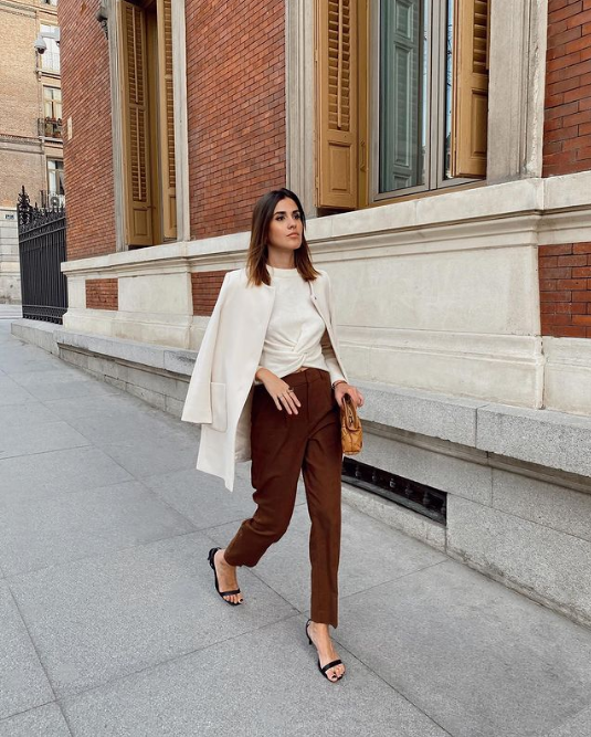 a white draped top, brown pants, black heels, a creamy long blazer and an amber bag for a spring to summer look