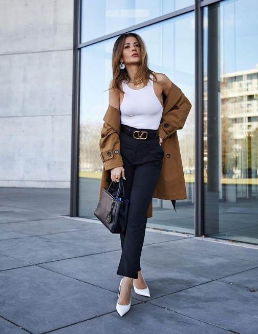 a white halter neckline top, black pants and a statement belt, white shoes, a black bag and a taupe short trench