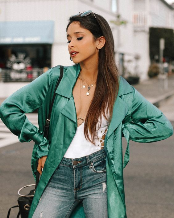 a white lace up top, blue jeans, layered necklaces and a green duster plus a black bucket bag