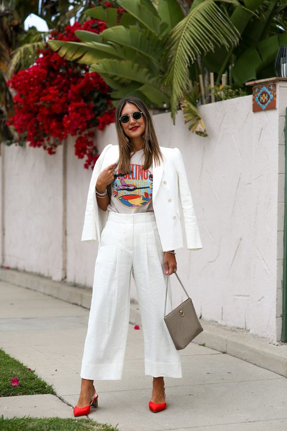 a white linen pantsuit with wideleg pants, a printed t shirt, red slingbacks and a grey bag