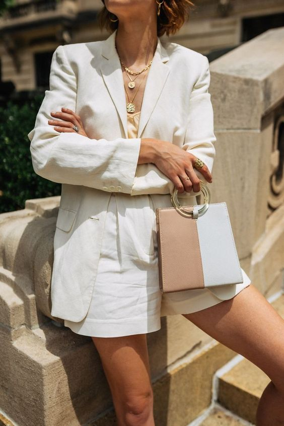 a white linen short suit with a neutral silk top, layered necklaces, a two tone bag