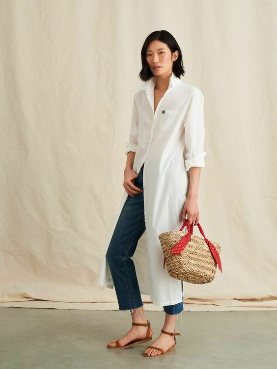 a white midi shirtdress, blue jeans, brown sandals and a woven bag with a bright ribbon for summer