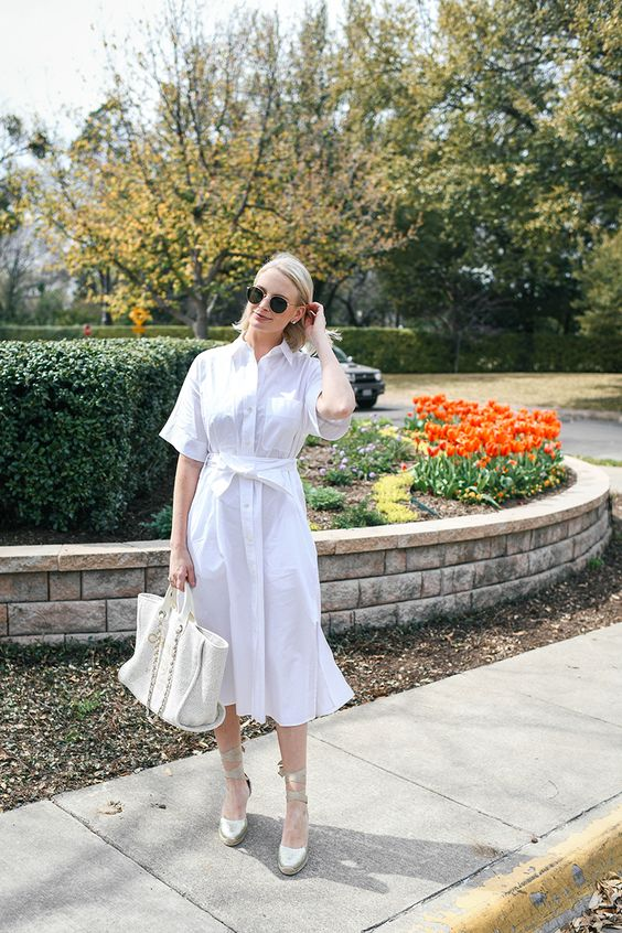 a white midi shirtdress with a sash, neutral espadrilles and a white tote for a summer work look