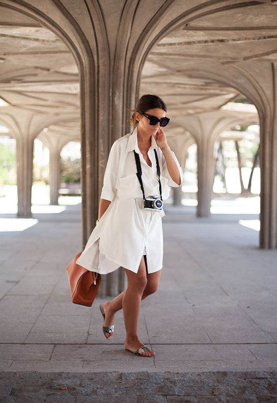 a white over the knee shirtdress, snakeskin slippers, an amber bag for a vacation look