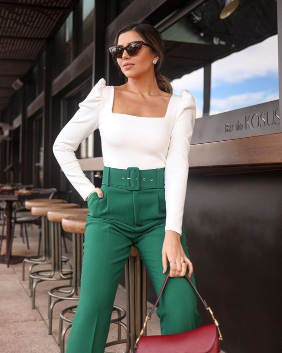 a white puff sleeve top with a square neckline, green high waisted trousers and a red saddle bag