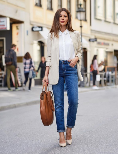 a white shirt, a neutral oversized blazer, blue jeans, nude heels and a brown round bag