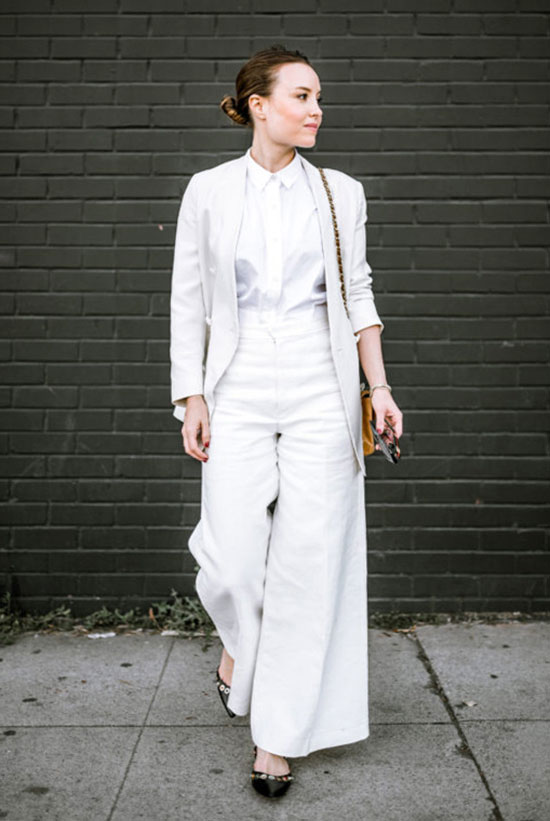 a white shirt, a white pantsuit with flare pants, black embellished flats and a bold bag