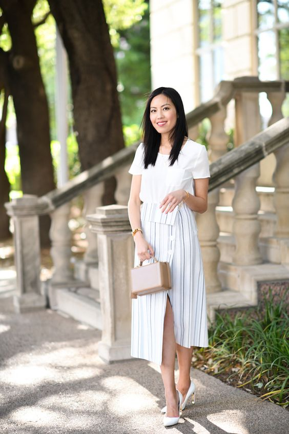 a white short sleeve top, a striped wrap midi skirt, white shoes and a tan mini bag