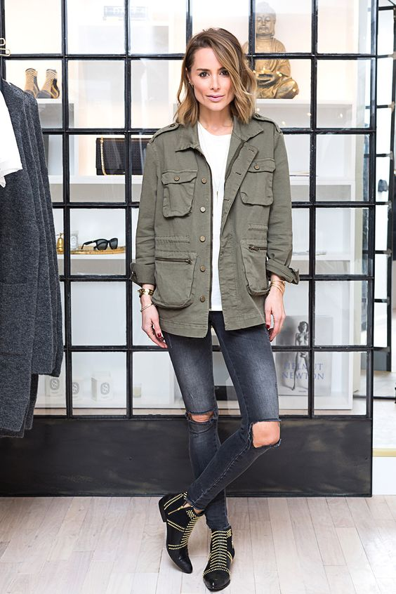 a white t-shirt, black ripped jeans, a green army jacket and black ambellished booties