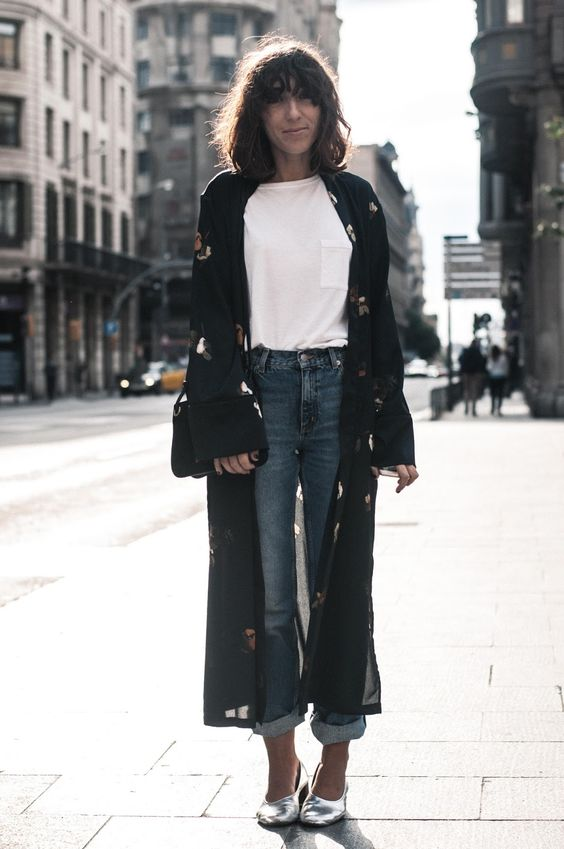 a white t-shirt, blue cuffed jeans, silver flats and a black floral print duster plus a black bag