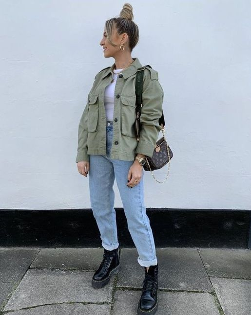 a white t shirt, light blue jeans, a green army jacket, black combat boots and a black bag