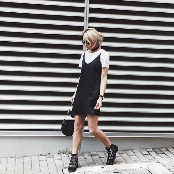 a white tee, a black slip mini, black buckle boots and a black saddle bag for a chic summer look