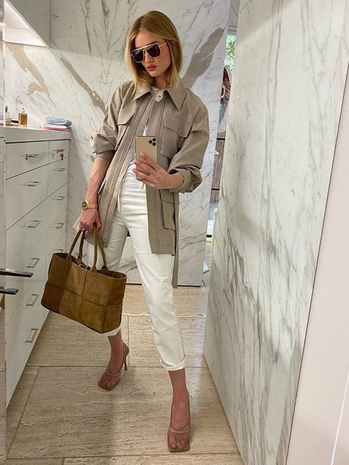 a white top and cropped trousers, tan square toe shoes, a grey safari jacket and a stylish suede bag