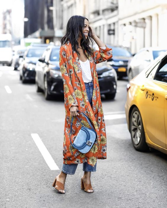 a white top, blue cropped jeans, brown mules, an orange floral duster and a blue bag