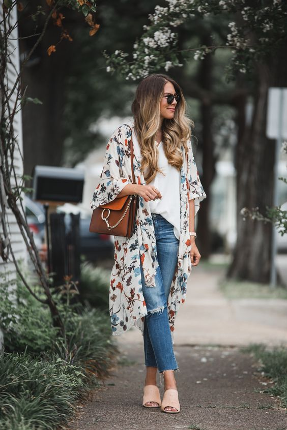 a white top, blue ripped jeans, blush mules, a white floral kimono and a brown ring bag