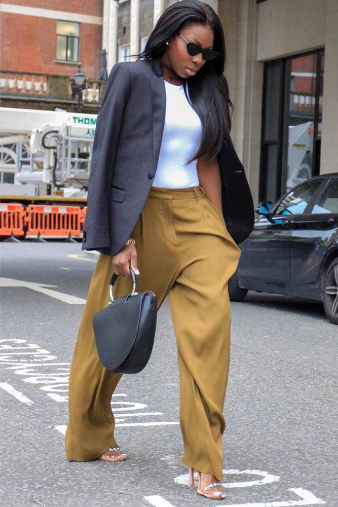 a white top, mustard colored palazzo trousers, a grey blazer and a black bag for a stylish look