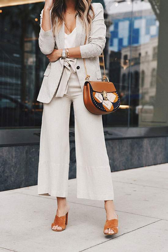 a white top, neutral pants, a thin stripe blazer, amber heeled mules and an amber printed bag