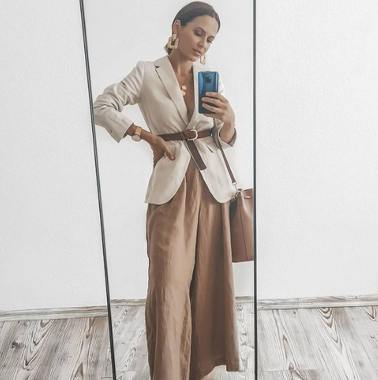 amber wideleg pants, a creamy oversized blazer with a brown belt, a brown bag and statement earrings