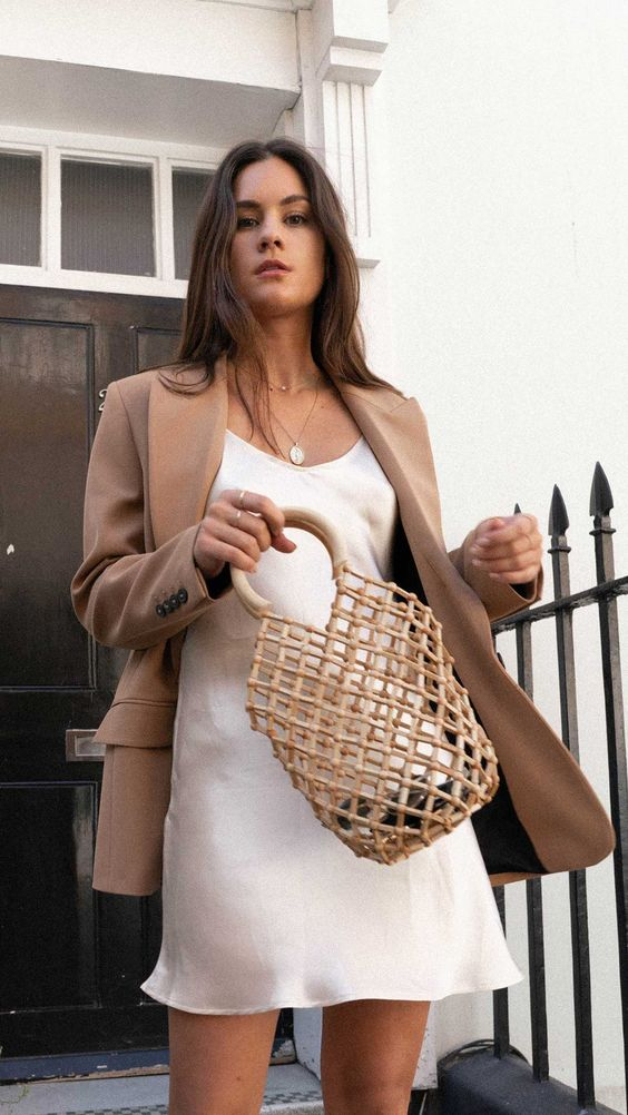 an ivory slip mini dress, a tan oversized blazer and a trendy woven bag for a chic and sexy look