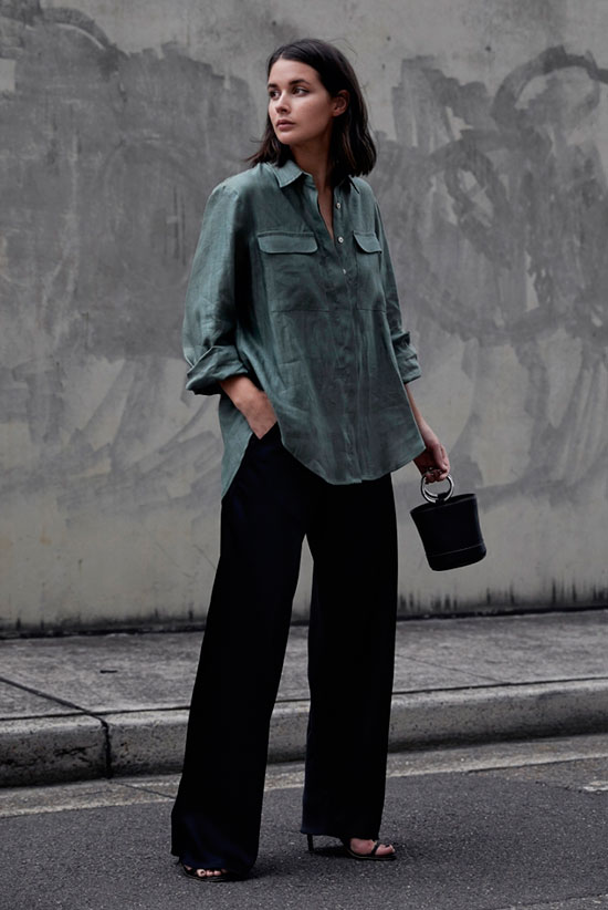 black pants, a green oversized shirt with pockets, a black bucket bag and elegant heels
