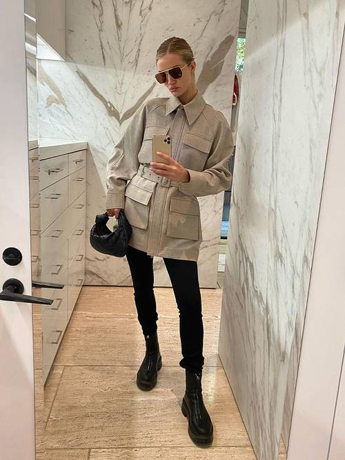black skinnies, black Chelsea boots, an off-white safari jacket with a belt and a small hobo bag