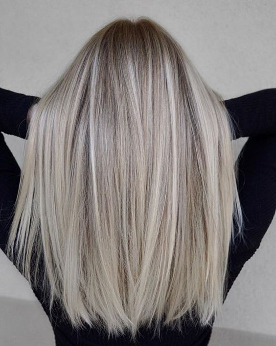 blonde hair with darker roots and silver champagne touches and highlights is a stylish and modern idea