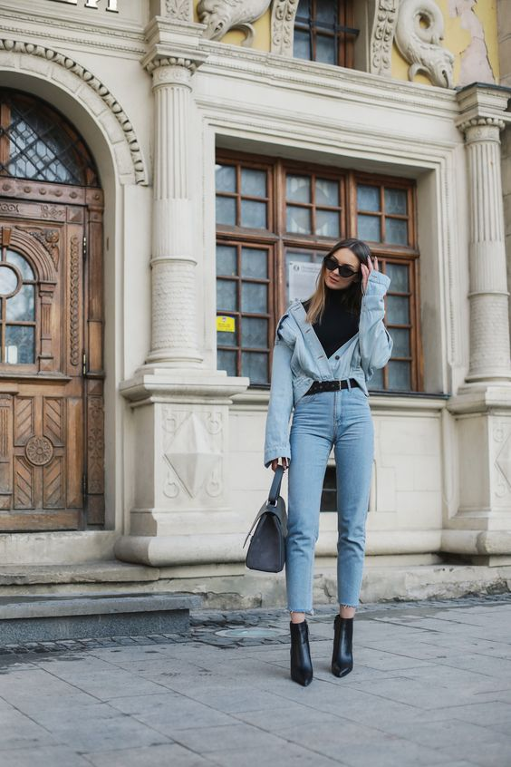 blue jeans, a blue chambray shirt put on over a black turtleneck, black booties and a grey bag